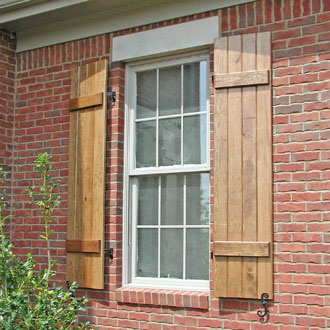 Wooden Stained Board and Batten Shutters on a Brick House
